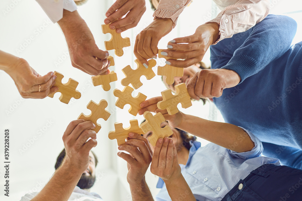 Fototapeta Positive company workers playing with jigsaw puzzle during team building activity