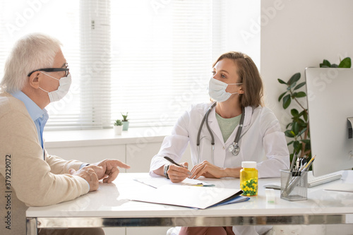 Young doctor in whitecoat and protective mask listening to senior patient #379229072