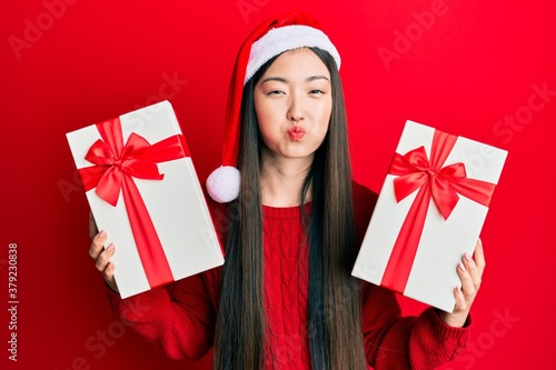 Fotomural Young chinese woman wearing christmas hat and holding gifts puffing cheeks with funny face