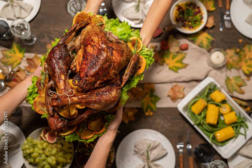 Fototapeta Top view of hands of young woman passing roasted turkey to her husband obraz