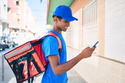 Valokuva African delivery man wearing courier uniform outdoors using smartphone