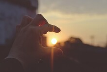 Woman's Hand Holding The Sun A...