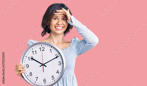 Young beautiful girl holding big clock stressed and frustrated with hand on head Fotobehang