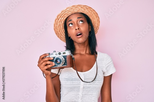 Photo Young african american woman wearing summer hat holding vintage camera looking sleepy and tired, exhausted for fatigue and hangover, lazy eyes in the morning