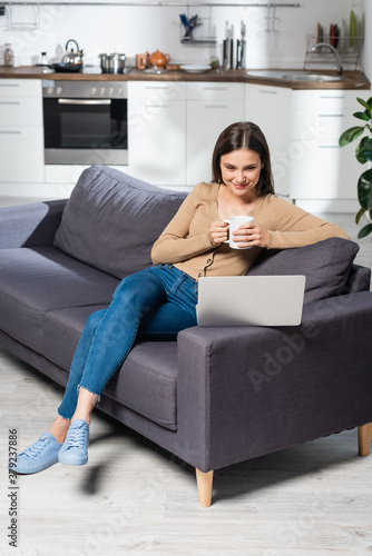 Fototapeta pleased freelancer holding cup of warm beverage while sitting on couch in kitchen near laptop obraz