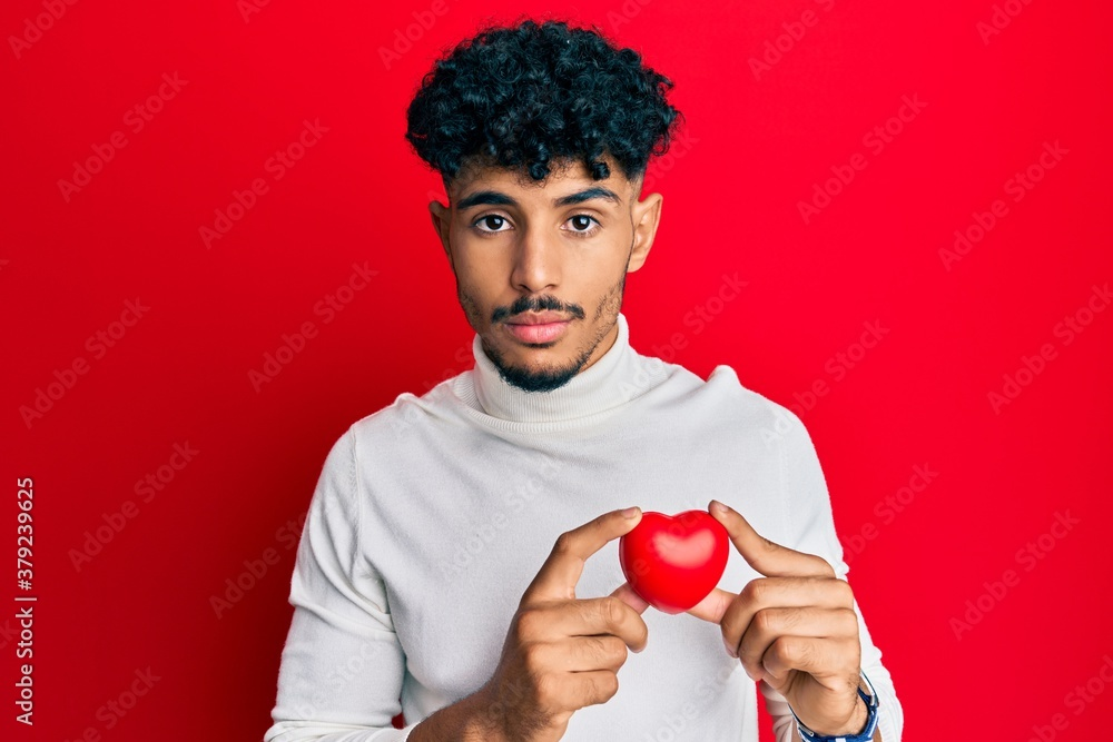Fototapeta Young arab handsome man holding heart relaxed with serious expression on face. simple and natural looking at the camera.