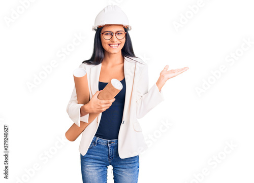 Young beautiful latin girl wearing architect hardhat holding blueprints celebrating victory with happy smile and winner expression with raised hands