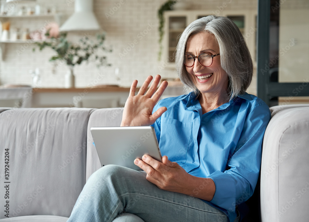 Fototapeta Happy 60s older mature middle aged adult woman waving hand holding digital tablet computer video conference calling by social distance virtual family online chat meeting sitting on couch at home.