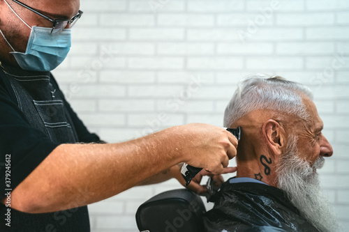 Male hairdresser cutting hair to hipster senior client while wearing face surgical mask - Young hairstylist working in barbershop during corona virus outbreak - Health care and haircut salon concept