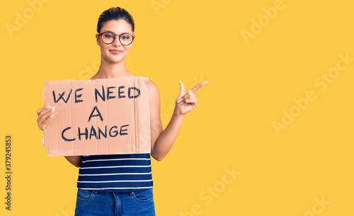 Fotografía Young beautiful woman holding we need a change banner smiling happy pointing wit