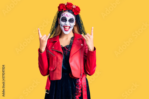 Vászonkép Woman wearing day of the dead costume over background shouting with crazy expression doing rock symbol with hands up