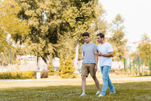 Man Gesturing While Walking And Talking With Teenager Son In Park
