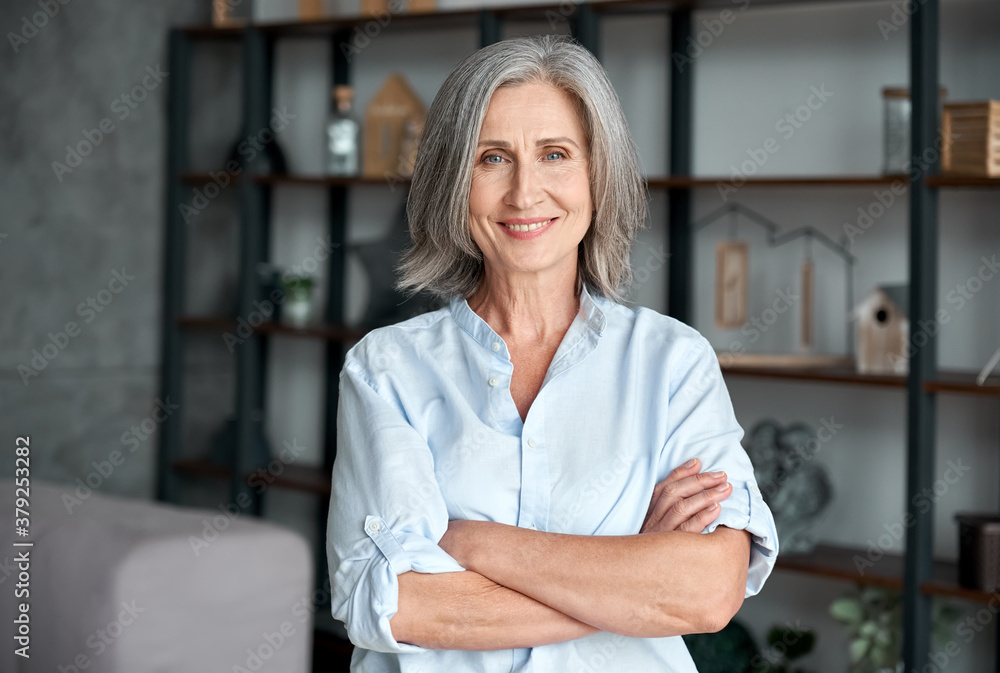Fototapeta Smiling confident stylish mature middle aged woman standing at home office. Old senior businesswoman, 60s gray-haired lady executive business leader manager looking at camera arms crossed, portrait.