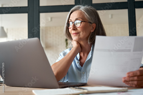 Smiling mature middle aged business woman using laptop working on computer sitting at desk. Happy old businesswoman hr holding cv interviewing distance applicant, senior seeker searching job online.