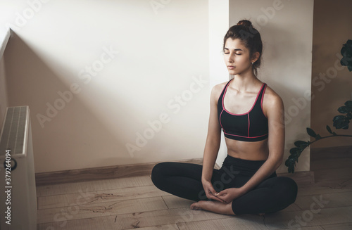 Fototapeta Home yoga session done by a caucasian woman in sportswear meditating on the floor near free space obraz