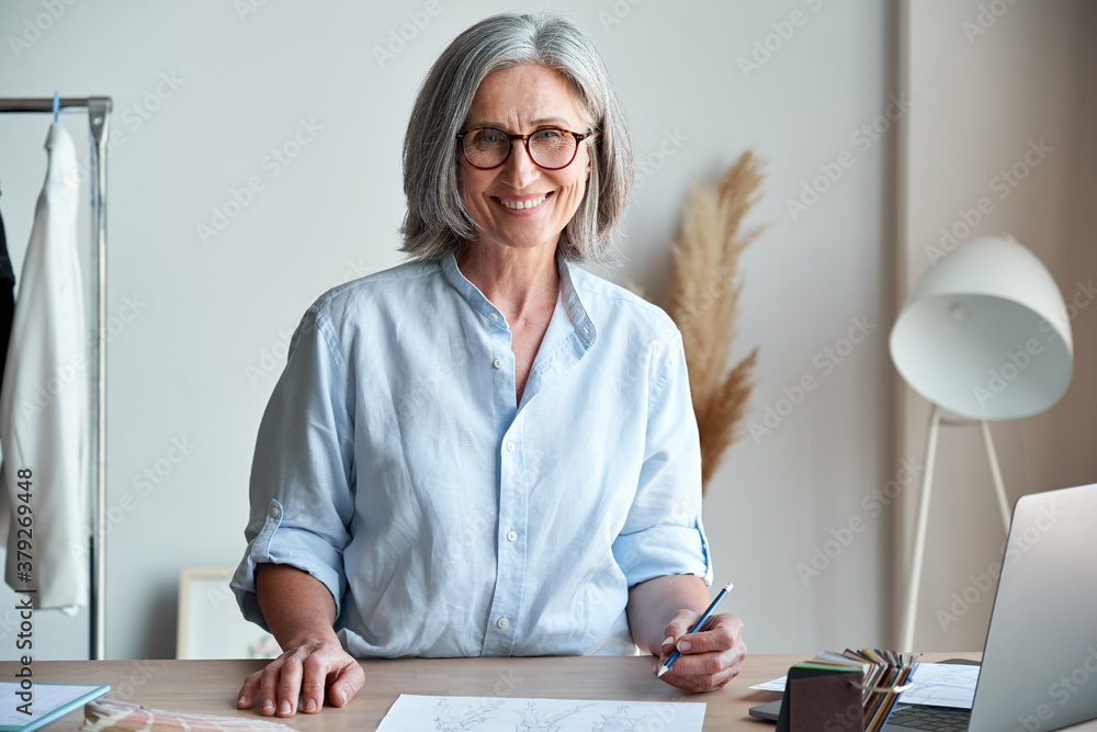 Fototapeta Happy middle aged stylish woman fashion designer wears glasses standing at workplace desk, portrait. Smiling sophisticated 60s old lady dressmaker drawing sketches, looking at camera in modern atelier