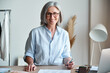 Happy middle aged stylish woman fashion designer wears glasses standing at workplace desk, portrait. Smiling sophisticated 60s old lady dressmaker drawing sketches, looking at camera in modern atelier