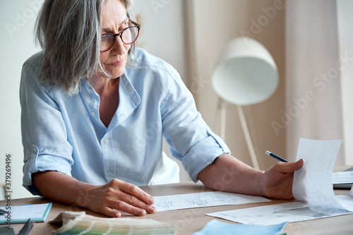 Fotografía Mature old adult elegant woman fashion designer drawing creative sketches on table