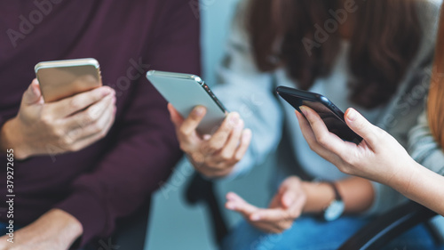 Fototapeta Group of young people using and looking at mobile phone while sitting together obraz