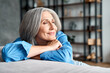 Happy relaxed mature old woman resting dreaming sitting on couch at home. Smiling mid aged woman relaxing. Peaceful serene grey-haired lady feeling peace of mind enjoying lounge on sofa and thinking.