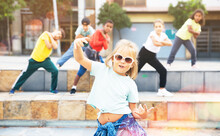 Little Girl Hip Hop Dancer In Casual Clothes And Sunglasses Exercising With Friends At Outdoors Dance Class