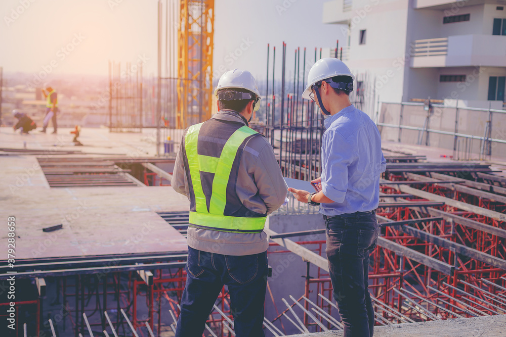 Fototapeta Structural engineer and foreman worker with touch pad discuss, plan working for the outdoors building construction site.