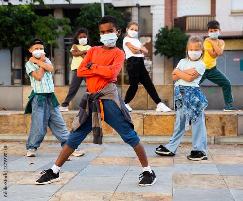 Obraz Modern tweens in protective face masks dancing hip-hop on summer street. New urban lifestyle concept during coronavirus. Conscious generation - fototapety do salonu