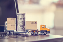 US USD 100 Dollar Bills, Boxes, A Trailer Truck On A Laptop Computer, Depicts Dispatching / Delivery Goods For Online Shopping, Customers Or Buyers Buy Product And Service From Internet Retail Store
