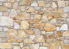 White And Orange Stone Wall Made Of Large Flat Natural Rocks. Background And Texture.