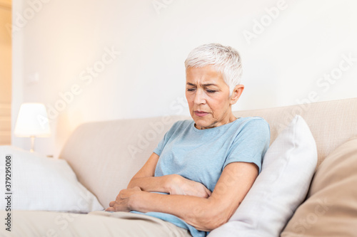 Photo Old age, health problem and people concept - senior woman suffering from stomach ache at home