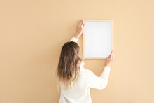 Woman Hanging Blank Photo Frame On Wall