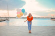 canvas print picture Young woman with balloons outdoors near river