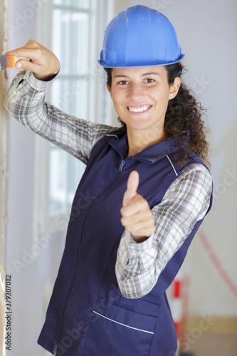 Fototapeta builder woman shows thumbs up obraz