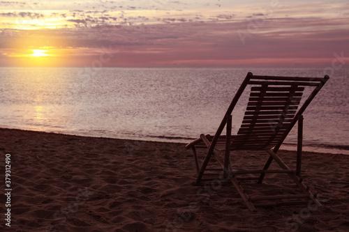 Fototapeta Wooden deck chair on sandy beach at sunset. Summer vacation obraz