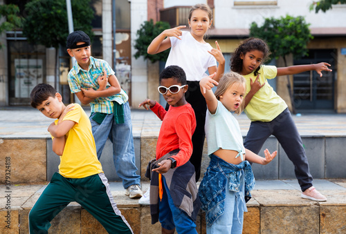 Positive girls and boys training hip hop on city street, outdoor dance class for kids