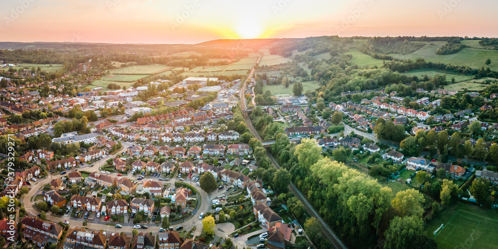 Fototapeta Aerial view of British town set in beautiful countryside in warm light of sunset