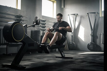 Athletic Male Do Hard Exercises With Rowing Machine .