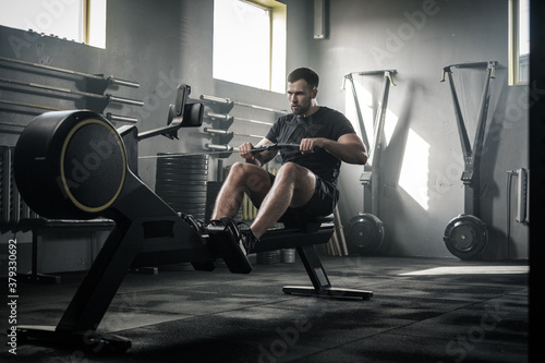 Fototapeta Athletic Male Do Hard Exercises With Rowing Machine . obraz