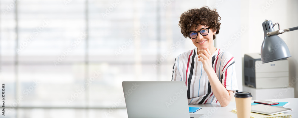 Obraz Portrait of business woman looking at camera at workplace in an office fototapeta, plakat