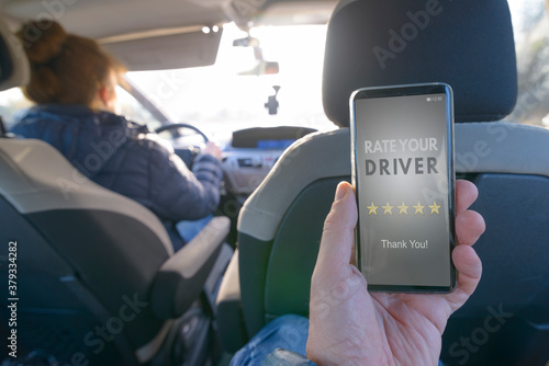Photo Passenger using smart phone app to rate a taxi or modern peer to peer ridesharin
