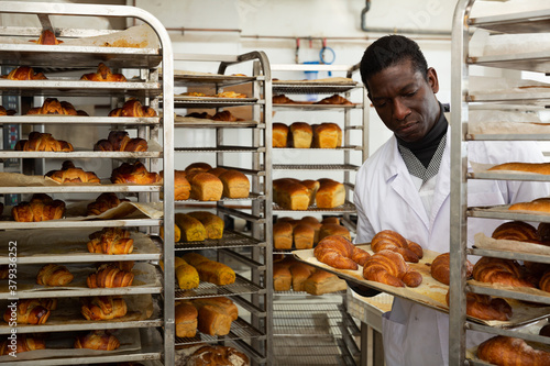 Photo Experienced african american baker placing tray with freshly baked rolls on rack trolley in small bakery
