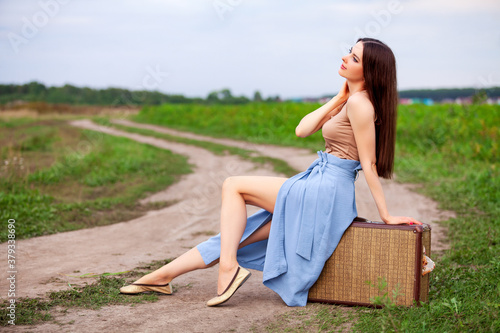 Pretty girl is sitting on an old suitcase on a country road #379338690