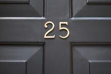 Brass Number Twenty Five Attached To Brown Wooden Panelled Door
