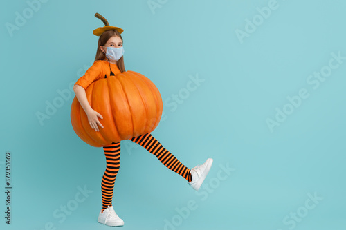 Photo girl in pumpkin costume  wearing face mask