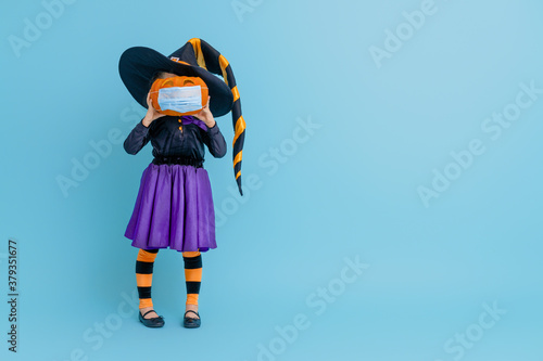 witch with a pumpkin  wearing face mask - 379351677