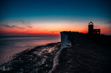 Sunset on edge of cliffs with lighthouse in the back and ocean - sea on horizon