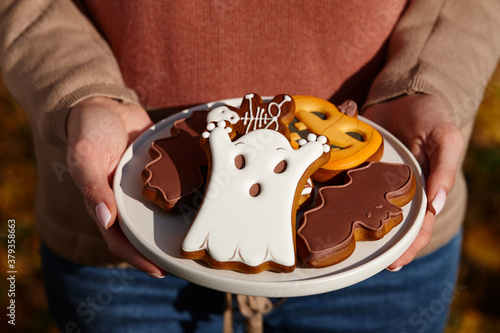 Foto Woman holding halloween gingerbread biscuits in plate, holiday sweets