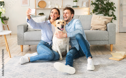 Fototapeta Young couple taking selfportrait with dog at home obraz