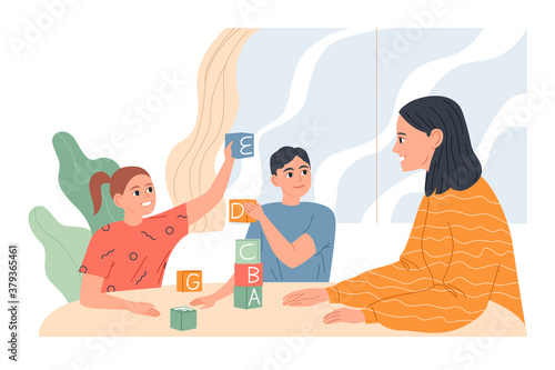Photo Young woman with children at the table playing and learning letters