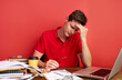 young stressed caucasian male working with computer laptop in frustration, depression.he has stress problems and despair at work, isolated on red background